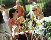 Women at a table in open air with drinks and pastries