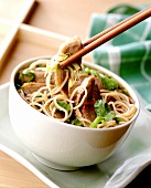 Duck on noodles with coriander leaves in bowl & on chopsticks