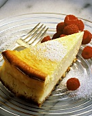 A piece of lemon cheesecake with icing sugar & raspberries