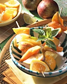 Fruit kebabs with ginger butter in a bowl