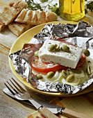 Grilled sheep's cheese in foil with tomato, onion, olive