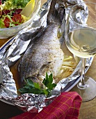 Whole sea perch in foil on platter; white wine glass; salad