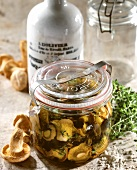 Pickled mushrooms in a pickling jar; Herbs, salt, oil