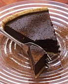 A piece of chocolate tart with cocoa powder on glass plate