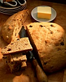 Raisin bread, a slice cut; knife; butter