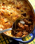 Meat ragout with potato topping in the baking dish