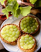 Three grape tartlets with vanilla cream on a plate