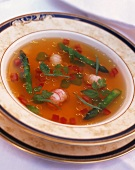 Crab soup with asparagus, diced tomatoes and fresh herbs