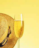 A champagne glass beside a straw hat