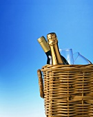 Champagne bottle and wine bottle with glasses in picnic basket