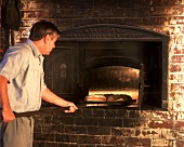 Baker taking freshly baked loaves out of wood-burning oven