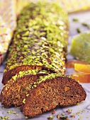 Chocolate roll (Rehrücken) with chopped pistachios (slices cut)