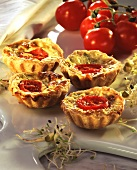 Sprout & quark quiches, topped with tomatoes, on marble board