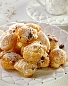 Grappa fritters with raisins & icing sugar on white plate