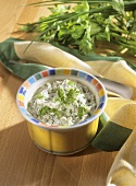 Curd cheese with herbs in bowl, cloth and fresh herbs behind