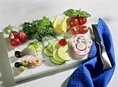 Vegetables, lemons & herbs for garnishing on marble; cloth