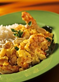 Shrimp curry with pineapple, almonds & rice on green plate