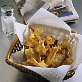 Deep-fried parsnip slices in a basket; Salt cellar