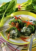 Spinach leaves stuffed with mince and coconut with tomato