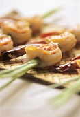 Scampi skewered on lemon grass on bamboo tray