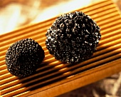Two black truffles on ribbed wooden board