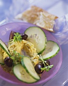Chick pea puree with cucumber slices and olives on plate