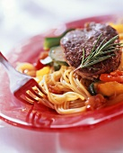 Fillet steak with spaghetti, courgettes, rosemary on plate