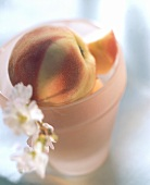 Peaches in a pink bowl; decoration: peach blossom
