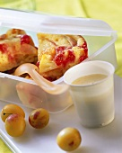 Polenta fruit bread in plastic box; custard in plastic pot