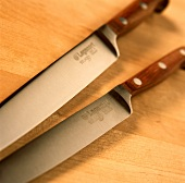 Two knives with wooden handles on wooden background
