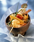 Shrimp kebabs with corncobs on rice in wooden bowl