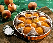 Peach tart with icing sugar in the baking dish