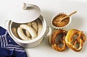 White sausages (Weisswurst) in pan, mustard and two pretzels