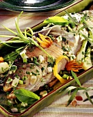 Salmon trout in herb sauce with mace in baking dish