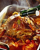 Basting roast pork & tomatoes with beer in roasting dish