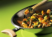 Sweet and sour Thai vegetables in a wok and on chopsticks