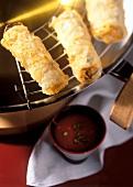 Vietnamese spring rolls on wok rack; tomato dip