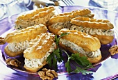 Eclairs with cheesy cream filling & walnut kernels on plate