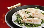 Fisch mit Spinat auf Teller im Wok dämpfen