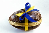 Chocolate Easter egg with yellow and blue bow