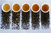Various small bowls of black tea with the relevant tea leaves