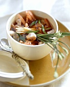 Asian vegetable soup with chives in small bowl; Spoon