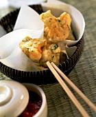 Deep-fried cauliflower on chopsticks & in bowl; dip