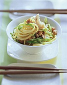 Spaghetti with fish and mangetouts in bowl; chopsticks
