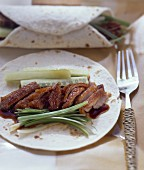 Peking duck with spring onions on pancakes