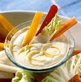 Lemon dip with vegetable sticks in glass bowl