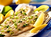 Trout in baking parchment with spring onions and lemons