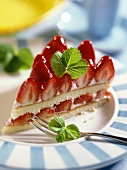 A whole piece of strawberry quark cake on a plate with a fork