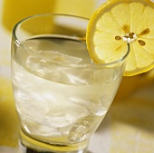 Cold lemon juice drink with lemon slice on the edge of the glass