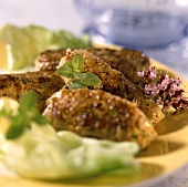 Grilled cevapcici with salad leaves on plate